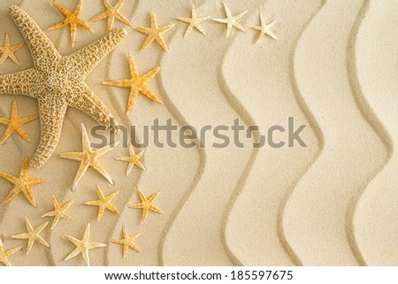 Scattered dried starfish in different sizes arranged to the left side on golden beach sand with decorative wavy lines in a nautical themed background - stock photo