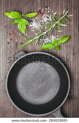 Scattered fresh basil and rosemary, sea salt and dry peppercorns near the frying pan - stock photo