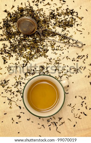 Scattered green tea leaves with tea cup and infuser - stock photo
