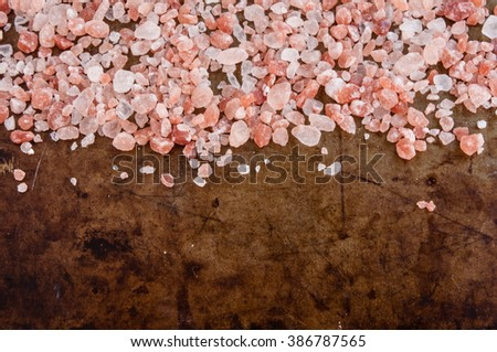 Scattered Himalayan pink salt crystals, top view on rusty metal background, space for text - stock photo