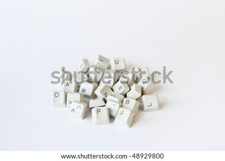 scattered keyboard keys on white background - stock photo