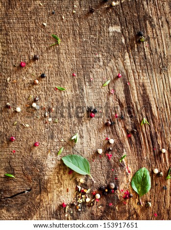 Scattered mixed peppercorns and basil lying on an old textured wooden surface in a country kitchen after preparing a meal - stock photo