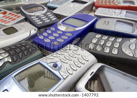 Scattered old mobile phone handsets. All makes and models in various states of disrepair. - stock photo