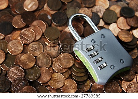 Scattered pennies with a padlock reading 2009 on it. - stock photo