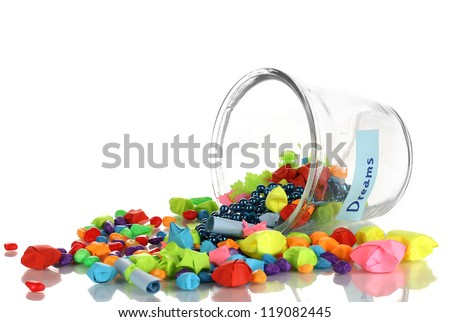 Scattered pieces of paper and colored stones with dreams in glass vase isolated on white - stock photo