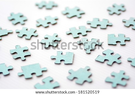 Scattered puzzle pieces toy isolated on white background. Concept photo of disharmony, change, no-order and chaos. - stock photo