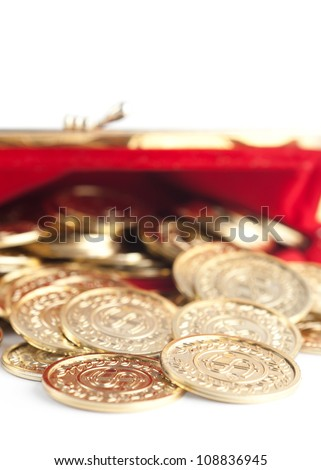Scattered silver and gold coins are in  hot red purse, isolated on white. A great number of coins symbolize wealth, richness, income and profit. Close up shot. - stock photo