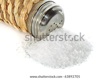 Scattered small group of salt and saltcellar on a white background - stock photo