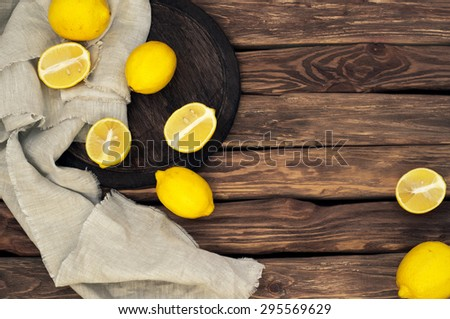 Scattered yellow lemons on the old wooden background. Rural or rustic style. top view. Copy space. free text space. close up. Old wooden table - stock photo
