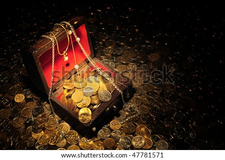 Scattering of coins around and inside trunk with treasure. - stock photo