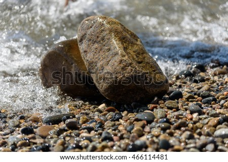 Scattering of colored  sea pebbles and big granite stones