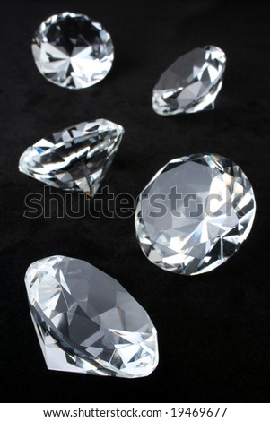 Scattering of round brilliant cut diamonds over black velvet - stock photo