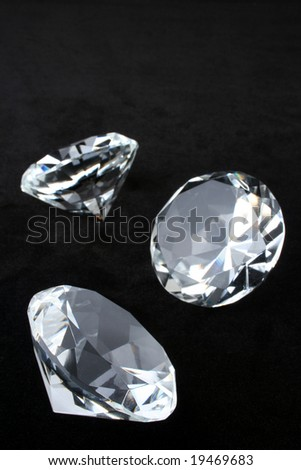Scattering of round brilliant cut diamonds over black velvet with copy space - stock photo