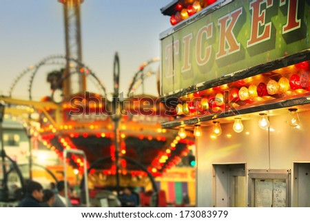 Scene at a classic carnival with a ticket booth in the foreground (focal point on the ticket sign) with overall subtle retro vintage tone and styling - stock photo