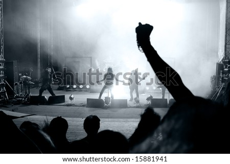 Scene from a rock concert with silhouette singer - stock photo