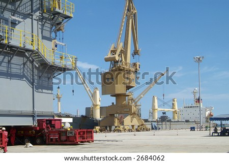 Scene from industrial port with freight ship, crane and big steel structure being moved by heavy-lift equipment.