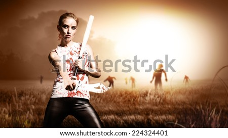 scene like in a horror movie with a woman holding a machete and a knife and standing on a field with approaching zombies  - stock photo