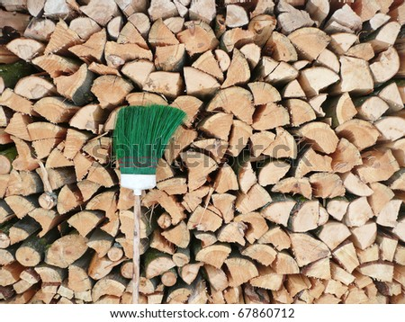 Scene of a farm: wood stack with a green broom - stock photo