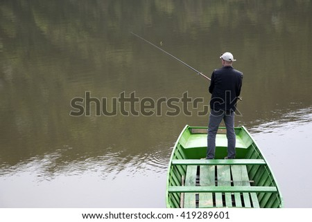 Scene Of Fisherman With His Back Towards Camera Fishing From The Boat On The Calm Lake, Water Reflection - stock photo