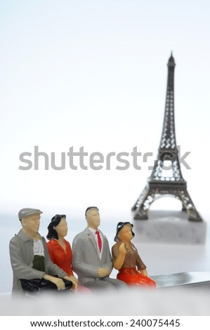Scene of french people miniature figures in front of Paris Eiffel tower - stock photo