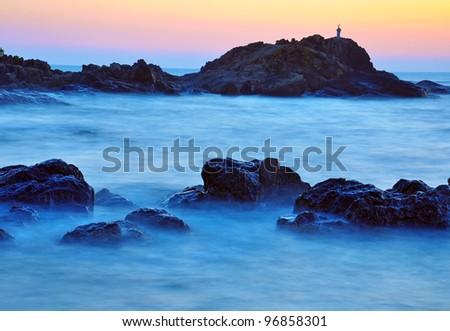 scene of ocean with rocks and smearing pattern of water movement - stock photo