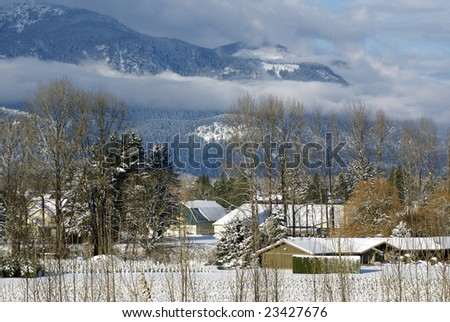 Scene of snowy Fraser Valley with fields, trees, farm buildings, mountains, and low clouds - stock photo