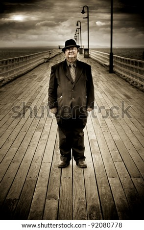 Scene Of Solitude With A Serious Older Man Standing Alone And In Seclusion On A Old Wooden Bridge During The Golden Years Of His Life - stock photo