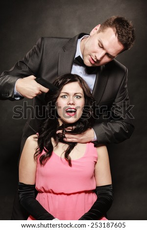 Scene of violence with firearm between men and women. Elegant man holding gun against sitting lady on black grey background in studio. - stock photo