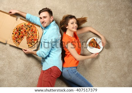 Scene simulation, young couple with pizza - stock photo