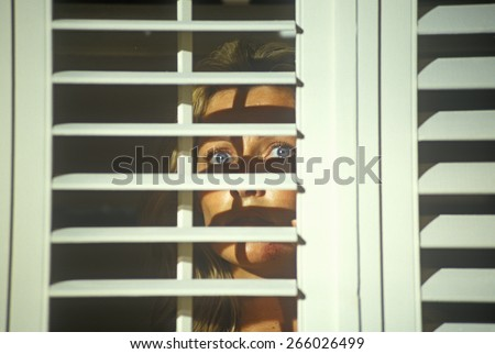 Scene with actress looking through blinds from set of 'Temptation', feature film, Miami, FL - stock photo