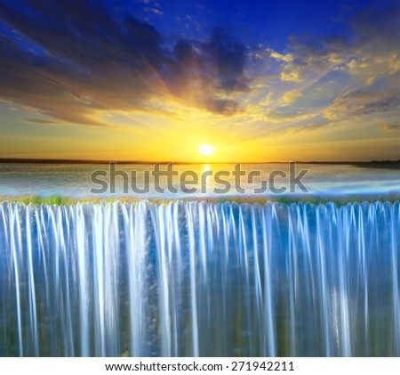 Scene with waterfall on sunset sky background - stock photo