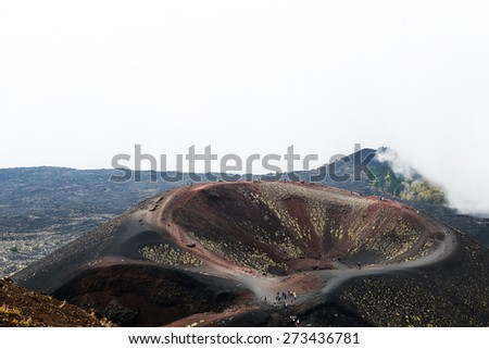 Scenery and craters Silvestri of Mt. Etna volcano, Sicily, with sporadic yellow grasses growing on black volcanic (igneous) rock and tourists walking to the crater.  - stock photo