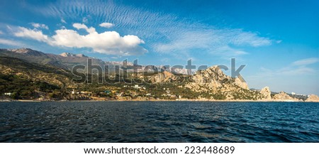 Scenery of Ai-Petri peak in Crimean mountains and Kacively resort from Black sea under blue sky with beautiful clouds; south coast of Crimea peninsula, Russia - stock photo