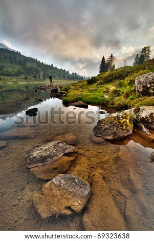 scenery of alpine lake with fisherman - stock photo