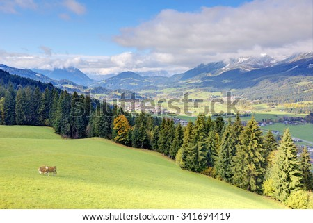 Scenery of an alpine ranch with village Ellmau in the valley and a mountain range in the distant background ~ Beautiful autumn landscape of Kaiser Mountains in Tirol, Austria, Europe - stock photo