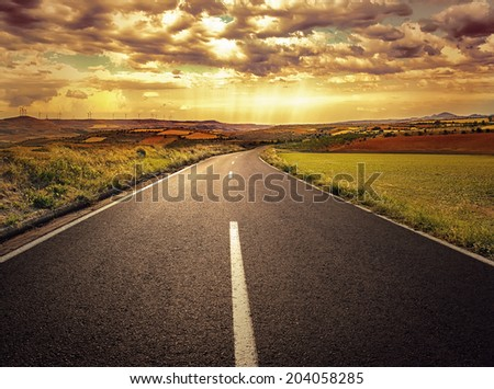 Scenery of asphalt road through agricultural fields.  - stock photo