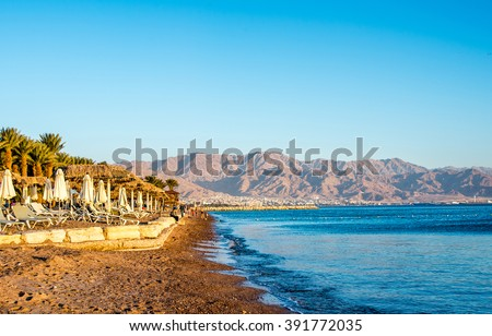 Scenery  of Eilat beach, Israel over Aqaba city, Jordan. - stock photo
