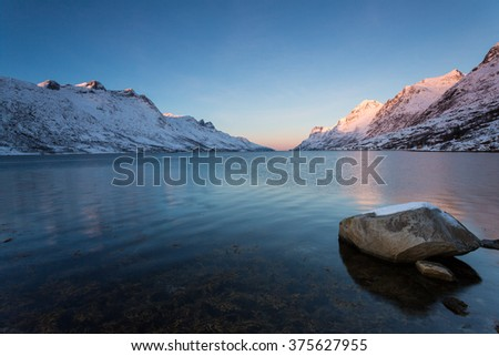 Scenery of fjord with high mountain in winter, Ersfjorden, Norway - stock photo