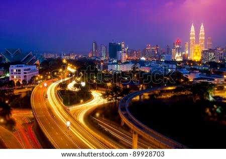 Scenery of Kuala Lumpur twin towers with stunning light trail from the busy highway traffic.