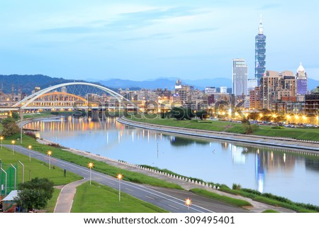 Scenery of Taipei City, Taipei 101 Tower in downtown area with arch Bridges and beautiful reflections on the smooth water of Keelung River ~ Romantic cityscape of Taipei at dusk by riverside  - stock photo