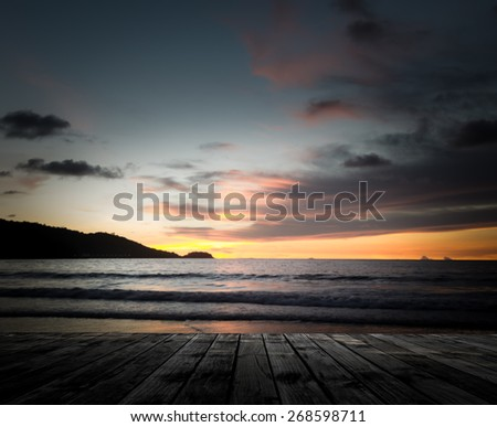 Scenery of wooden pier with dramatic sky sunrise above the sea - stock photo