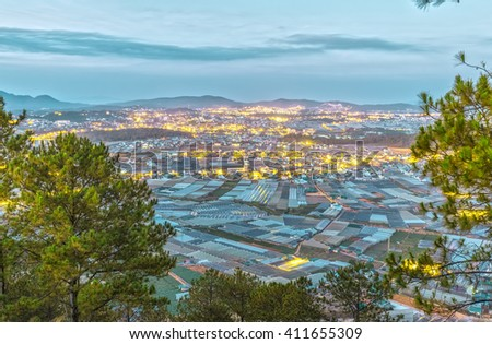 Scenes in highlands Da lat night with hundreds greenhouse and lights down in valley interwoven pine forest next to it great to watch from above - stock photo