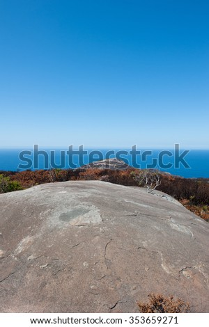 Scenic aerial coastal view of Torndirrup National Park, Albany, Western Australia, burnt vegetation, Southern Ocean, blue sky, copy space. - stock photo