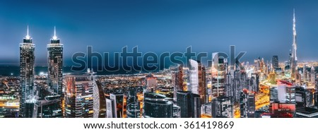 Scenic aerial nighttime cityscape with illuminated architecture of Dubai downtown, United Arab Emirates. - stock photo