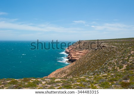 Scenic Aerial panorama of rough rock formation along coast of Kalbarri National Park in Western Australia, with wild waves of Indian Ocean crashing cliff, blue sky, horizon, copy space. - stock photo