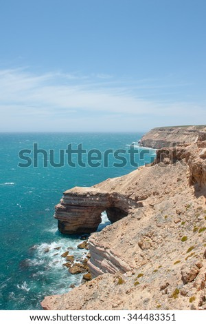 Scenic Aerial panoramic view of rock formation along coast of Kalbarri National Park in Western Australia, with wild Indian Ocean crashing against  cliff, summer sunny blue sky, horizon, copy space. - stock photo