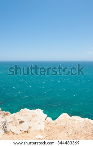 Scenic Aerial panoramic view of rugged rock formation at steep coast of Kalbarri National Park in Western Australia, wide open Indian Ocean summer sunny blue sky, horizon, copy space. - stock photo