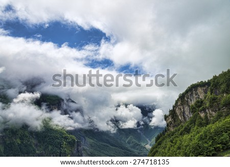 Scenic aerial view of green alpine canyon with trees growing on edge - stock photo
