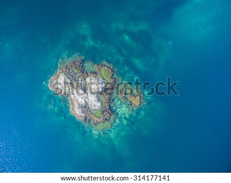 Scenic aerial view of tiny rocky islet in turquoise sea - stock photo