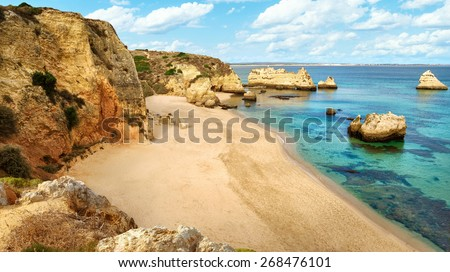 Scenic beach paradise at the Atlantic with the clear, blue green water of the ocean and high cliffs with warm colors. The sky is a nice bright blue with white clouds. Shot in Lagos, Portugal - stock photo
